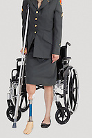 Low section of a female US military officer with crutch standing in front of wheelchair over gray background