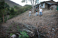Luis Carlos ( R ) shows the eradicated coca bushes he removed himself in return for alternative crops. He is participating in a program of the UN. He has serious doubts it will succeed. Two previous rounds of voluntary eradication turned out into a waste of money.  <br /> The region is controlled by the ELN guerrilla group. There's no official authority in town.