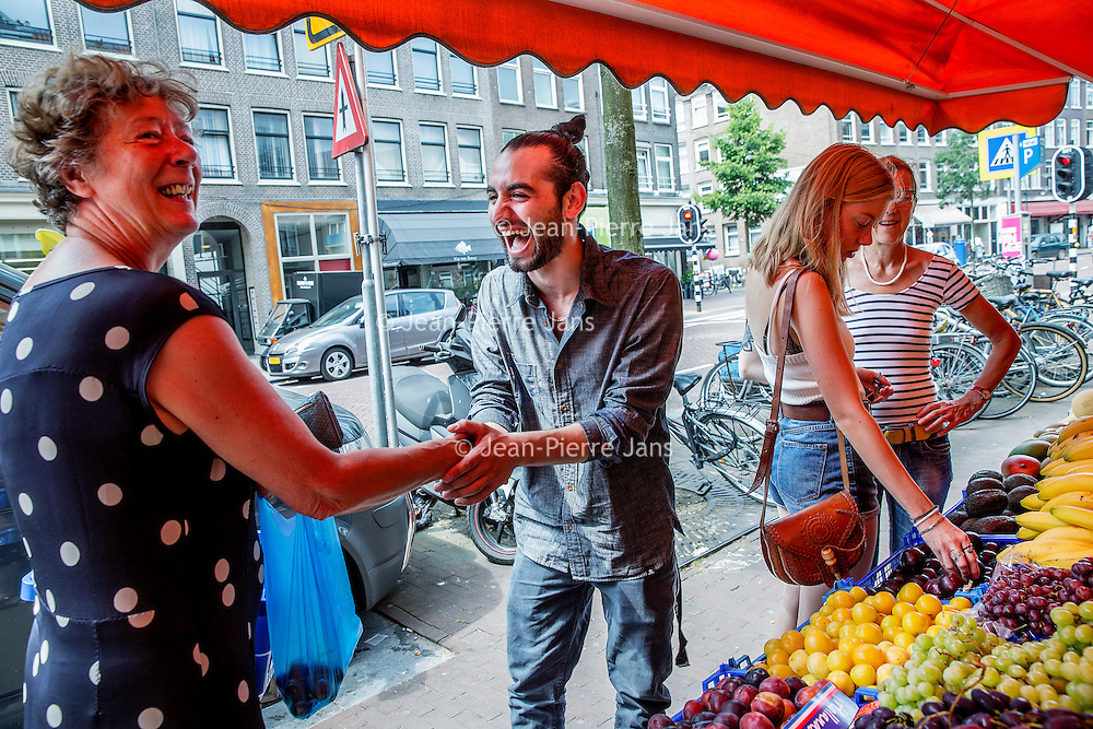 Nederland, Amsterdam, 23 juli 2016.<br />We volgen de Syrische jongen Ibrahim Najjar in de Spaarndammerbuurt in zijn zoektocht naar de ingredienten voor het Syrische kipgerecht Mskhan, een Syrisch ovengerecht met kip, citroen en ui.<br />Hij heeft zijn buren uitgenodigd bij hem te komen eten.<br />Op de foto: Ibrahim maakt een praatje met een buurtbewoonster bij kruidenier Kardeslar Market in de Spaarndammerstraat.<br /><br /><br /><br /><br />Foto: Jean-Pierre Jans