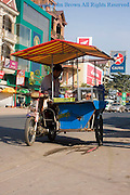 A man is selling street food from a mobile food cart on a city street in Kampong Cham, Cambodia.