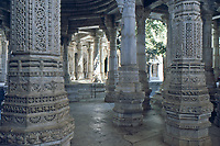 carved pillars in jain temple. Jain architecture in Ranakpur temple, Rajasthan, India. Glimpse trough engraved marble pillars of the adinatha temple