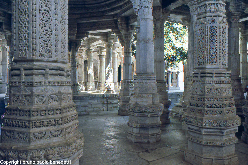jain architecture in Ranakpur temple, Rajasthan, India. Glimpse trough engraved marble pillars of the adinatha temple
