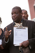A local activist appeals to people gathered during a vigil outside the North Charleston City Hall to register to vote and throw out the mayor following the shooting death of Walter Scott April 10, 2015 in Charleston, South Carolina. Scott was shot multiple times by police after running from a traffic stop.
