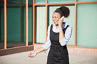 Cheerful young woman in formals using mobile phone