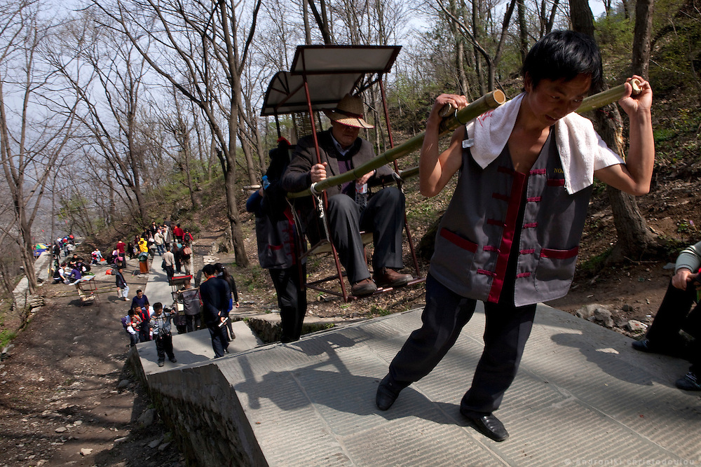 Asia, China, Hubei province.  The way to the top of Wudang moutain (Wudang-san), is hard and trvellers have to climb thousands of steps. Some chose the easy way up by paying local men to carry them on special chairs.