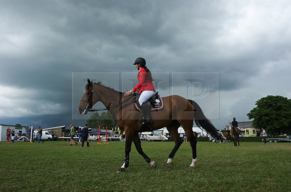 © Licensed to London News Pictures. <br /> 08/07/2014. <br /> <br /> Harrogate, United Kingdom<br /> <br /> A woman warms up her horse prior to competing on the first day of the Great Yorkshire Show. The show is England's Premier Agricultural Event and is based on the 250-acre Great Yorkshire Showground near Harrogate. The Main Ring is the hub of the Show providing a setting for international show jumping and world class cattle parade. The showground is filled with animals, country demonstrations, have-a-go activities and rural crafts.<br /> <br /> Photo credit : Ian Forsyth/LNP
