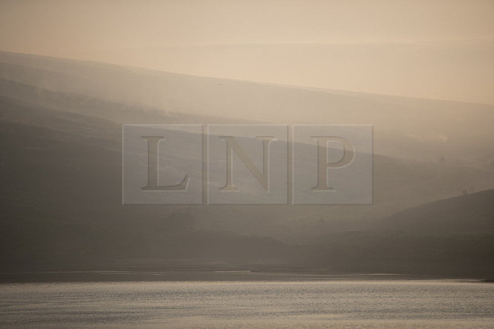 "© Licensed to London News Pictures . 28/06/2018 . Saddleworth , UK . Smoke fills the sky above the Moors as viewed across Higher Swineshaw Reservoir . The army are being called in to support fire-fighters , who continue to work to contain large wildfires spreading across Saddleworth Moor and affecting people across Manchester and surrounding towns . Very high temperatures , winds and dry peat are hampering efforts to contain the fire , described as "" unprecedented "" by police and reported to be the largest in living memory . Photo credit: Joel Goodman/LNP"