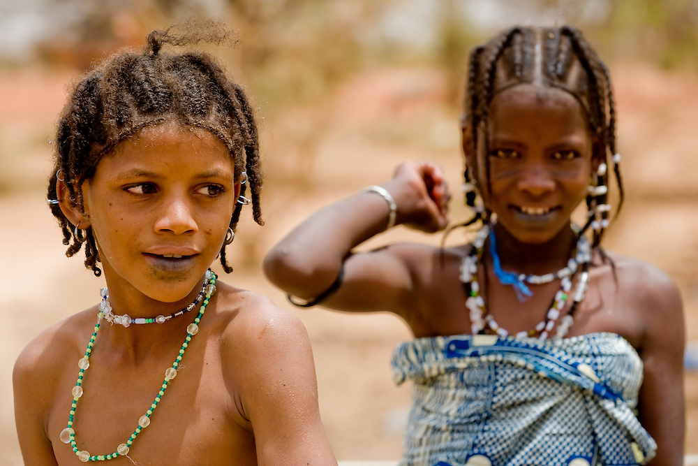 Young Fulani girls at the communal water pump for their family. The Fulani or Peuhl are nomadic herdsmen of the Sahel region of West Africa. The darker lower lip from indigo staining, facial tattoos and silver jewellery are traditional markings of Fulani women.
