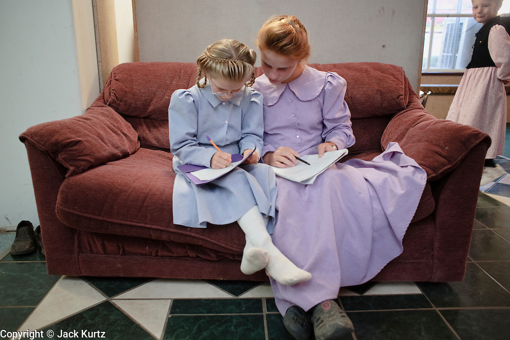 """Sept 8, 2008 -- COLORADO CITY, AZ: Girls in the Jessop family finish their homework before home schooling starts in their home. Members of the FLDS pulled their children from the public schools several years ago, now most of the families in town home school their children. The Jessops have almost 40 youngsters, in grades kindergarten through 8th grade, in their home school. Colorado City and the neighboring town of Hildale, UT, are home to the Fundamentalist Church of Jesus Christ of Latter Day Saints (FLDS) which split from the mainstream Church of Jesus Christ of Latter Day Saints (Mormons) after the Mormons banned what they call """"Celestial Marriage"""" (polygamy) in 1890 so that Utah could gain statehood into the United States. The FLDS Prophet (leader), Warren Jeffs, has been convicted in Utah of """"rape as an accomplice"""" for arranging the marriage of teenage girl to her cousin and is currently on trial for similar, those less serious, charges in Arizona. After Texas child protection authorities raided the Yearning for Zion Ranch, (the FLDS compound in Eldorado, TX) many members of the FLDS community in Colorado City/Hildale fear either Arizona or Utah authorities could raid their homes in the same way. Older members of the community still remember the Short Creek Raid of 1953 when Arizona authorities using National Guard troops, raided the community, arresting the men and placing women and children in """"protective"""" custody. After two years in foster care, the women and children returned to their homes. After the raid, the FLDS Church eliminated any connection to the """"Short Creek raid"""" by renaming their town Colorado City in Arizona and Hildale in Utah. The Jessops are a polygamous family and members of the FLDS.   Photo by Jack Kurtz / ZUMA Press"""