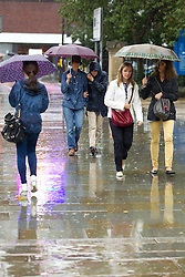 © Licensed to London News Pictures. 15/08/2012 . Manchester , UK .  A sudden , heavy , summer rain shower gets people reaching for their umbrellas following the previous day's sunshine and high temperatures . Photo credit : Joel Goodman/LNP