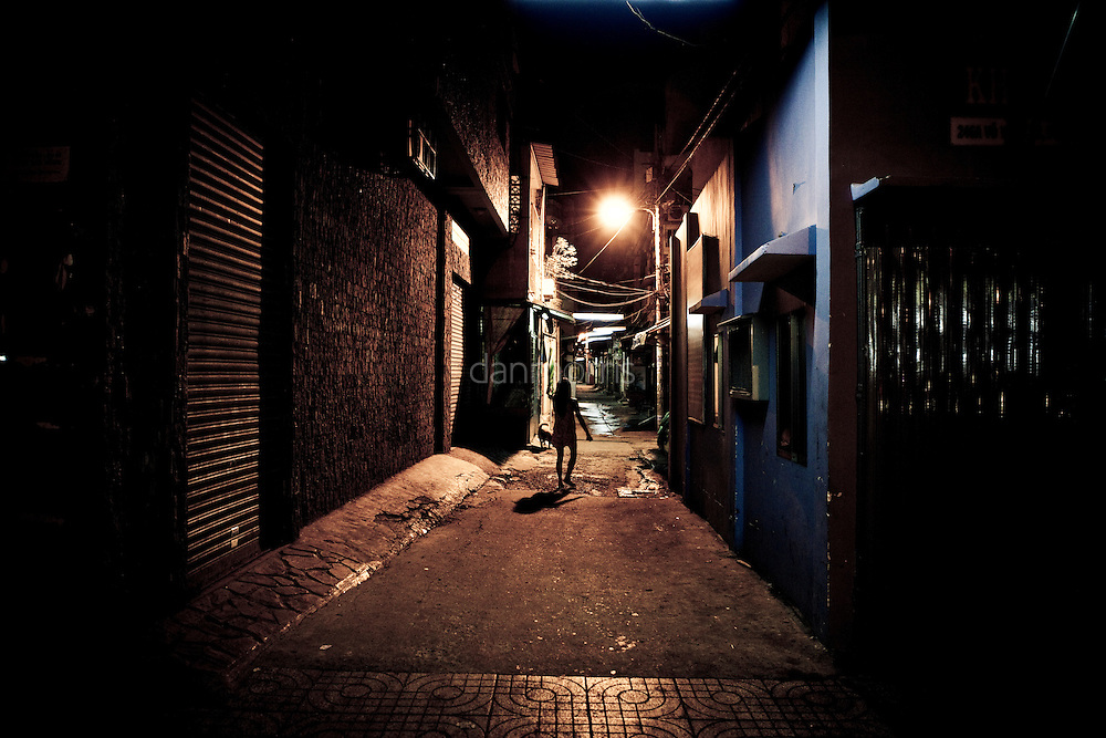 Young girl walks barefoot down alleyway late at night, Saigon, Vietnam