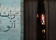 A coke machine and a styrofoam cup from Dunkin Donuts can be seen through the doorway of a garage.  Arabic writing is on the cinderblock wall outside.