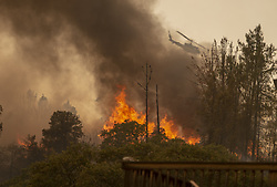 July 30, 2018 - Lakeport, California, U.S. - A helicopter flies over a home engulfed in flames on Pine Ridge Road, in unincorporated Lake County, west of Lakeport. (Credit Image: © Sacramento Bee via ZUMA Wire)