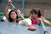 Young white and Asian teens age 15 washing cars for fund raiser.  Mound Minnesota USA