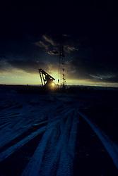 sun rising behind an on-shore rig
