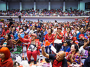 """23 FEBRUARY 2014 - NAKHON RATCHASIMA (KORAT), NAKHON RATCHASIMA, THAILAND: Thai Red Shirts gather in Liptapunlop Hall in Nakhon Ratchasima. The United front of Democracy against Dictator (UDD or Red Shirts), which supports the elected government of Yingluck Shinawatra, staged the """"UDD's Sounding of the Battle Drums"""" rally in Nakhon Ratchasima (Korat) to counter the anti-government protests that have gripped Bangkok since November. Around 4,000 of UDD's regional and provincial coordinators along with the organization's core members met at Liptapunlop Hall inside His Majesty the King's 80th Birthday Anniversary Sports Complex in Korat to discuss the organization's objectives and tactics against anti-government protestors, which the UDD says """"seek to destroy the country's democracy."""" The UDD leadersa announced that they will march to Bangkok and demonstrate against anti-government protests led by Suthep Thaugsuban.   PHOTO BY JACK KURTZ"""