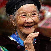 Ae elderly lady at the Lung Khau Nhin Market. Vietnam. Lung Khau Nhin Market is rural tribal market hiding itself amongst the mountains and forests of the far north Vietnam about 10 km from the border with China. The market plays an important role for the local ethnic people, Flower Hmong, Black Zao, Zay, and very small ethnic groups  Pa Zi, Tou Zi, Tou Lao. Tourist trips to the market run from Sapa and Lao Cai every week. Lung Khau Nhin Market, Vietnam.15th March 2012. Photo Tim Clayton