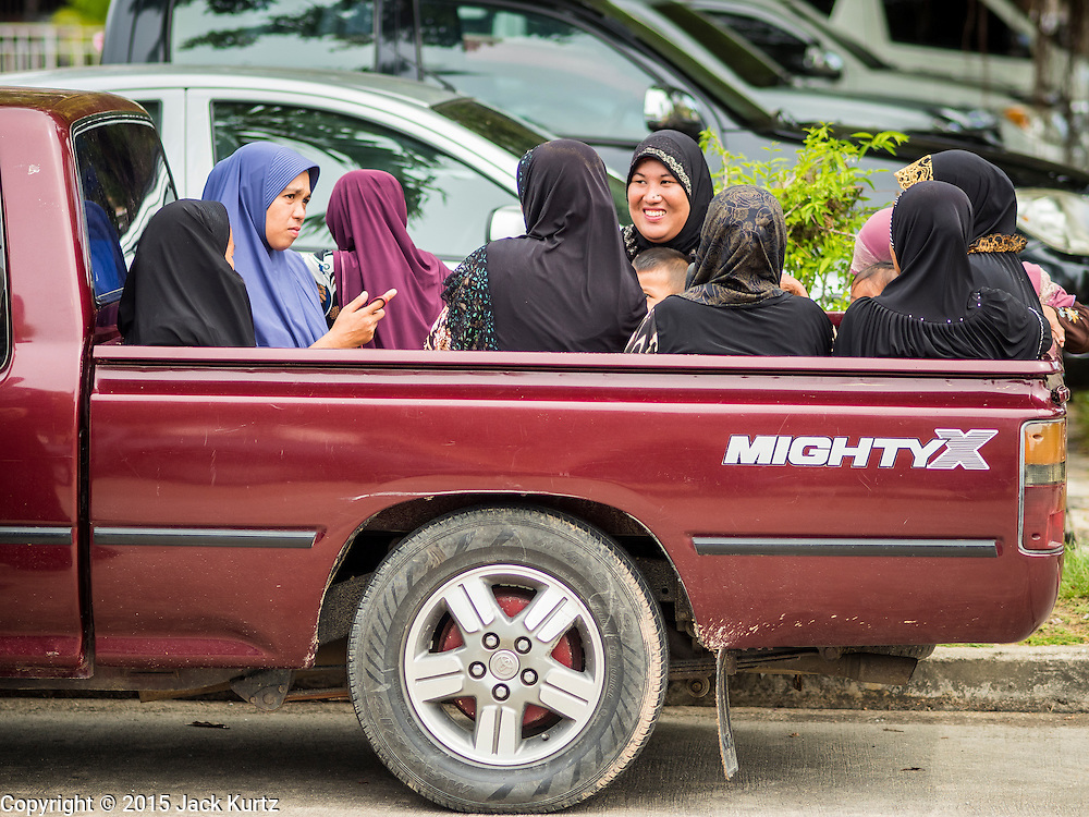 14 JUNE 2015 - NARATHIWAT, NARATHIWAT, THAILAND: Thai Muslim women arrive at a food distribution event in Narathiwat. The food distribution is held before Ramadan, which starts June 18. The annual food distribution event is organized by the Southern Peace Media Club, a group of Thai journalists who work in the southern provinces of Pattani, Narathiwat and Yala. An insurgency pitting Muslim extremists against the Thai government has rocked Thailand's southern three provinces since 2001. More than 6,000 people have been killed in the sectarian violence.    PHOTO BY JACK KURTZ