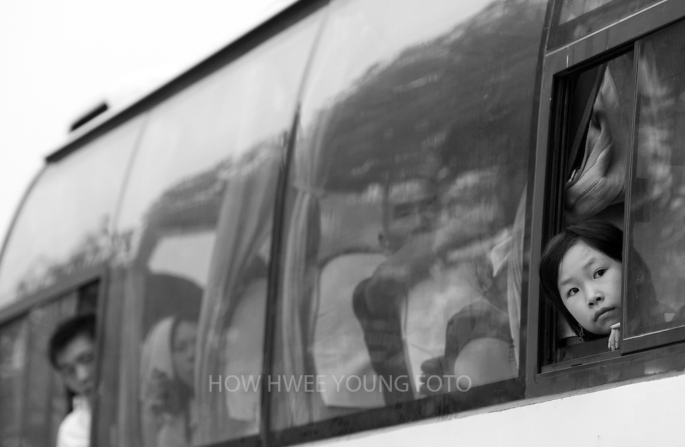 A migrant villager of Cangfang town look out from the bus on their way for relocation to neigbouring Hui county, more than 500 kilometers away, to make way for the colossal South-to-North Water Transfer project in Xichuan county of Henan Province in China on 29 June 2010. The South-to-North Water Transfer project, the largest known water diversion project, was conceived in 1952 to solve the country's chronic water shortages and involves creating three routes to channel 44.8 billion cu m of water from southern China to the northern areas. As part of the project's central route, affecting Henan and Hubei provinces, water from the Danjiangkou reservoir will be diverted to Beijing. The central route, which will raise the height of the Danjiangkou reservoir dam from 162 meters to 176.6 meters, requires the relocation of 330,000 people in Henan and Hubei provinces. Parts of Xichuan county, a remote, mountainous region inaccessible by railway and home to 162,000 migrants, the most anywhere, will be completely submerged by water from the Danjiangkou reservoir by 2014. The vast resettlement of affected residents in Xichuan county began in August 2009 and lasted till 2011.