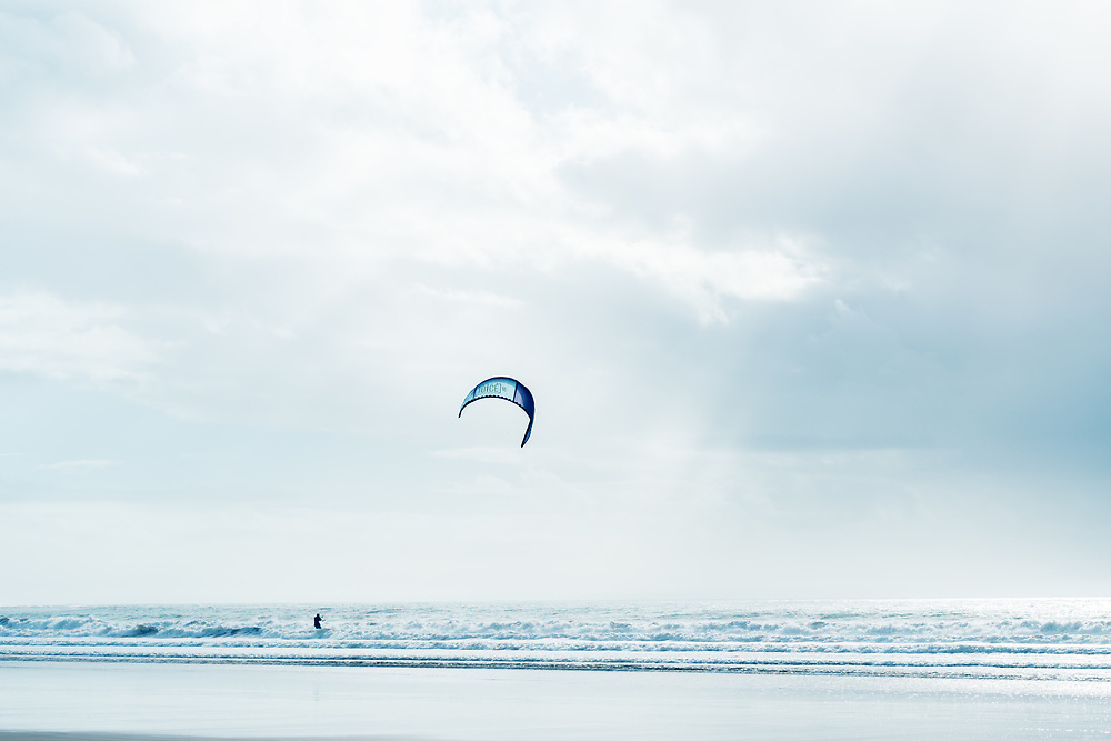 Kite surfer in the sea with cloudy sky. High key image.