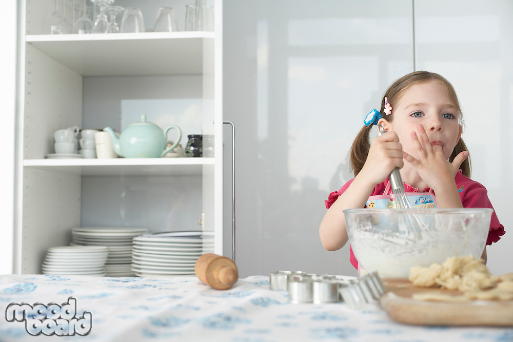 Girl (5-6) preparing food in bowl using wire whisk and licking finger