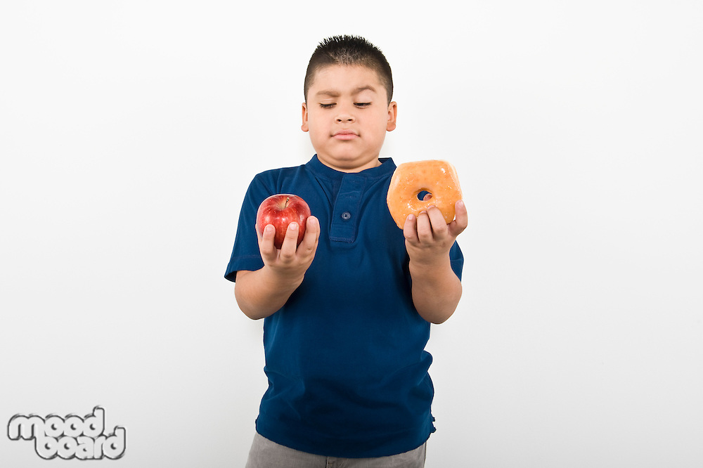 Pre-teen (10-12) boy holding doughnut and apple