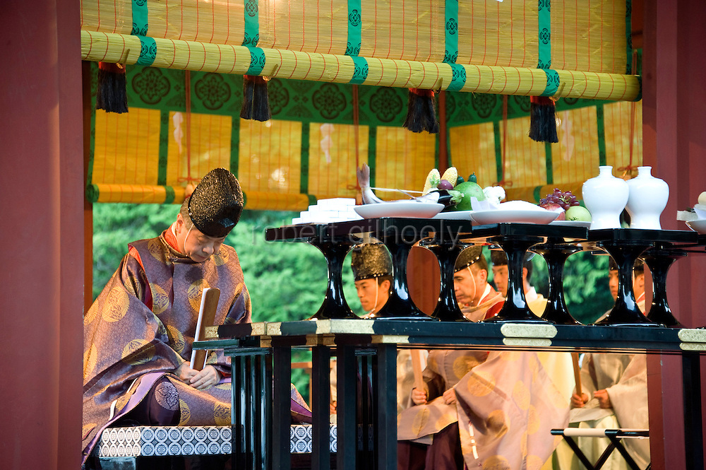 A shrine priest  bows in front of offerings of fish, fruit and sake rice wine during a ritual held to close the third day of the 3-day Reitaisai grand festival in Kamakura, Japan on  16 Sept. 2012.  Photographer: Robert Gilhooly