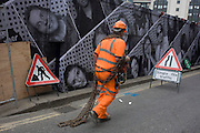A construction site contractor carries heavy chains along the street in front of a hoarding featuring many faces.