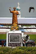 A worker uses a machete to trim shrubbery around a golden statue of martyred Archbishop Oscar Romero across from the Plaza El Salvador Del mundo (Savior of the World) where preparations are being made for Saturday's ceremony and mass announcing the beatification of Archbishop Oscar Romero. The Archbishop was slain at the alter of his Church of the Divine Providence by a right wing gunman in 1980. Oscar Arnulfo Romero y Galdamez became the fourth Archbishop of San Salvador, succeeding Luis Chavez, and spoke out against poverty, social injustice, assassinations and torture. Romero was assassinated while offering Mass on March 24, 1980.