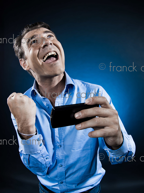 caucasian man portrait happy success with cellphone isolated studio on black background