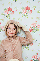 Portrait of young girl (5-6) in bunny costume touching ear wallpaper with floral pattern in background