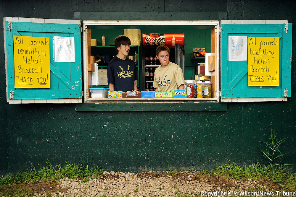Kris Wilson/News Tribune<br /> Helias baseball players Ben Mitan, left, and John McDonald wait patiently for new customers, or any customers for that matter, to stop by as they take their turn working the concession stand during Parochial Athletic League (PAL) youth baseball games at Whitener Field.