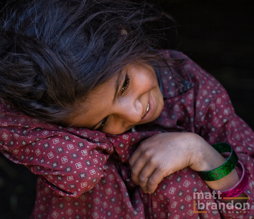 A young Bakarwal, Gujjar girl lays her head on her knee.
