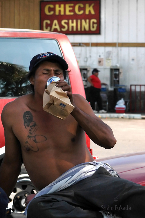 A migrant farm worker drinks after work in Immokalee, FL, Apr. 17, 2003.