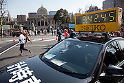 Runners pass a time car during t he 10th Tokyo Marathon took place on a fine spring day in Tokyo Japan. Sunday February 28th 2016. Thirty-six thousand runners took part with Ethiopian,  Feyisa Lilesa winning the  men's competition and  Kenyan, Helah Kiprop victorious in the women's race.