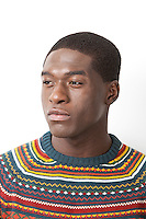 Thoughtful young man in knitwear looking away against white background