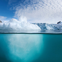 Norway, Svalbard, Spitsbergen Island, Underwater view of iceberg floating near glacier-covered mountains inside Fuglefjorden