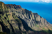 Kalalau Valley & Pacific Ocean, seen from Pihea Trail on Na Pali Coast, Kauai, Hawaii, USA. The potholed Pihea Trail traverses a spectacular cliff edge of Na Pali-Kona Forest Reserve, overlooking the Kalalau Valley in Na Pali Coast State Park down to the Pacific Ocean, a breathtaking 4000 feet below, on the island of Kauai. Slippery wet clay makes this a challenging hike of 2.6 miles round trip with 500 feet gain to Pihea Peak. (Optionally continue past Pihea Peak to Alaka'i Swamp Trail.) Pihea Trail begins at Pu'u O Kila Lookout at the end of the road in Koke'e State Park.