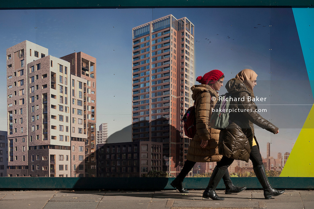 Two women walk past a regeneration project hoarding at Elephant Park, at Elephant & Castle, London borough of Southwark. Southwark Council's development partner, Lendlease is regenerating over 28 acres across three sites at the heart of Elephant & Castle, in what is the latest major regeneration opportunity in zone 1 London. The vision for the £1.5 billion regeneration is to build on the area's strengths and vibrant character in order to re-establish Elephant & Castle as one of London's most flourishing urban quarters. The Elephant & Castle regeneration is of a scale rarely seen in central London and includes almost 3,000 new homes, plus office, retail, community, leisure and restaurant space.