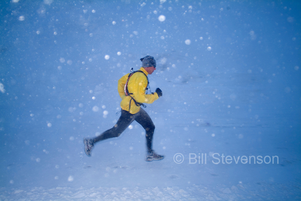 A photo of a man running in a snowstorm.