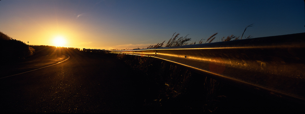 South Africa, Cape Town, Setting sun lights road guardrail along Signal Hill