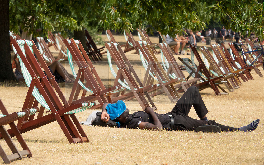 © Licensed to London News Pictures. 27/07/2018. London, UK. A man covers his face with a cloth as he lies in the sunshine in Hyde Park. Rain is expected later to break the heatwave in parts of the south. Photo credit: Peter Macdiarmid/LNP