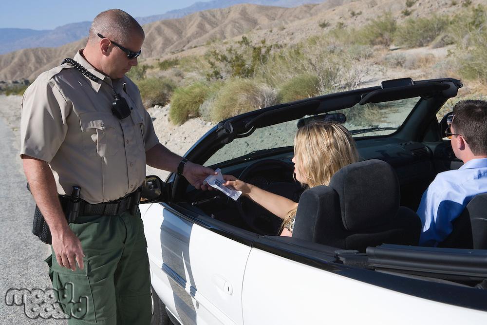 Policeman giving couple speeding ticket