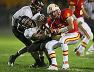 Marion's Tyler Gunderson (5) is hit by Solon's Danny Whitmore (59) after intercepting a pass during the first half of the game between the Solon Spartans and the Marion Indians at Thomas Park Field in Marion on Friday evening, October 5, 2012.