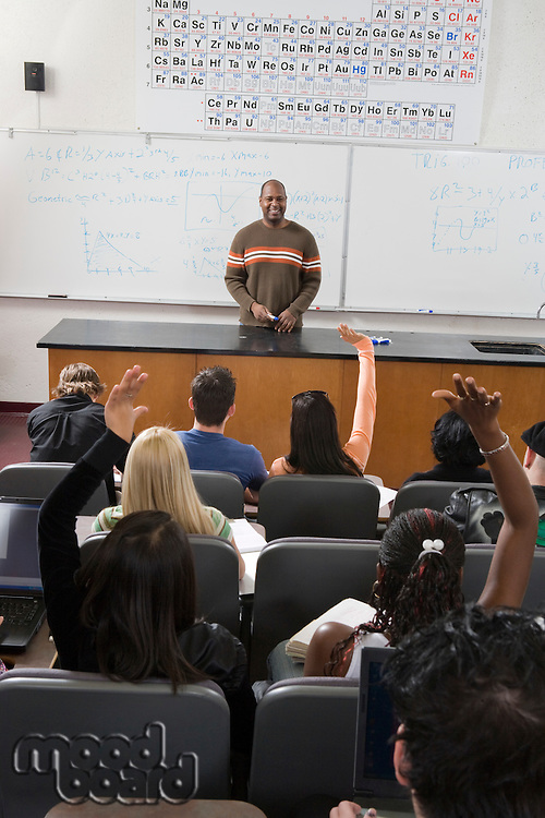 University students raising hands in class