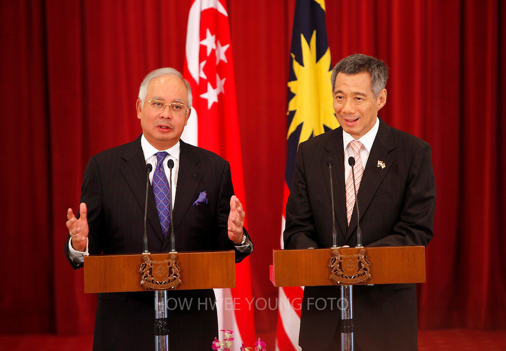 epa01738259 Malaysia's Prime Minister Najib Razak (L) speaks as Singapore's Prime Minister Lee Hsien Loong listens during a press conference after their meeting at the Istana in Singapore 22 May 2009. The Malaysian Prime Minister is in the city state for a two-day official state visit.  EPA/HOW HWEE YOUNG