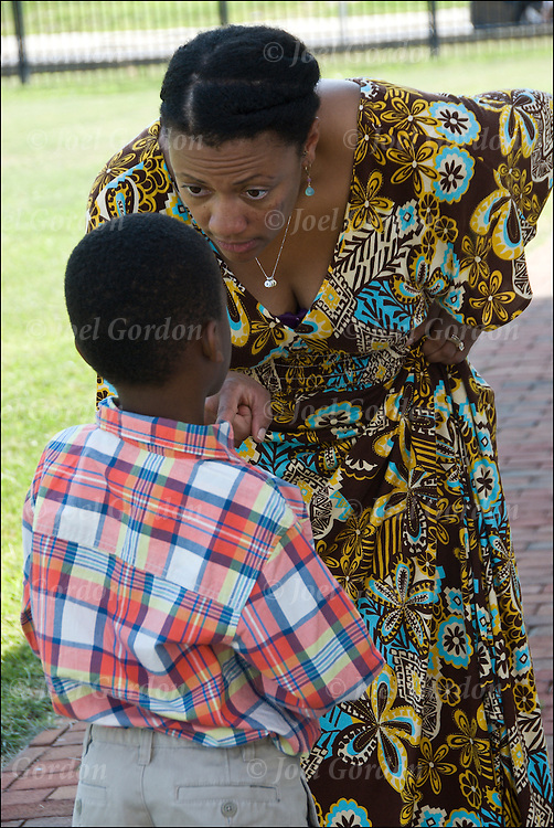 African American mother taking her son aside talking and showing her disapproval with his behavior at wedding.