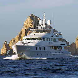 "The large luxury private yacht ""Primadonna"" cruising near land's end in Cabo San Lucas, Mexico."