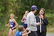 While his son tugs at his pants, Washington Huskies associate head track coach and 2004 Olympic pole vault silver medalist Toby Stevenson talks to UW director of operations Stephanie Bohannon, as Shona McCulloch (1274) and Katie Rainsberger pass by during the women's 3 mile run at the UW/Seattle University Open at Warren G. Magnuson Park., Friday, Aug. 30, 2019, in Seattle. (Paul Merca/Image of Sport)