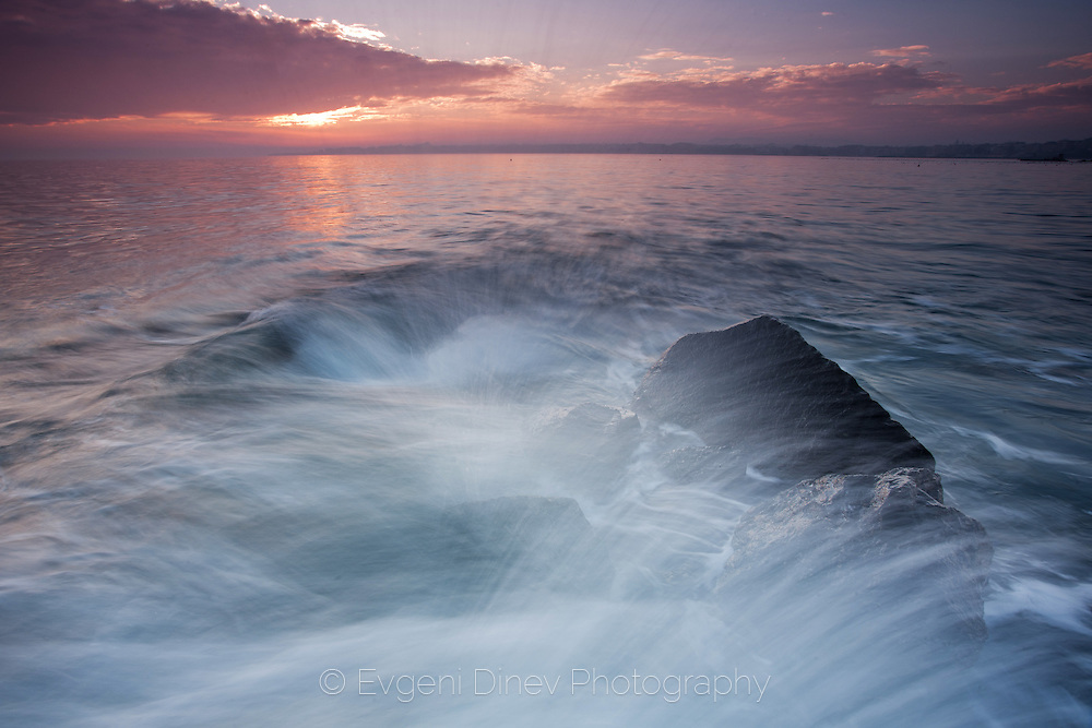 A wave splashing in the rock at sunset